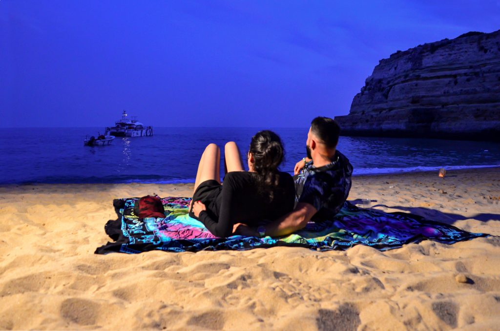 couple enjoying view at sunset beach bbq by algarexperience